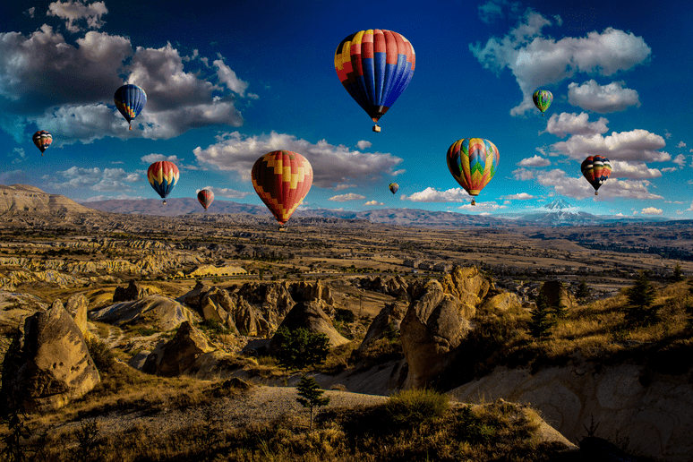 air balloons hanging over mountains