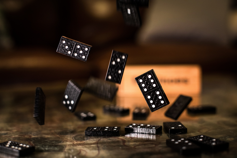 hand stopping wooden domino fall