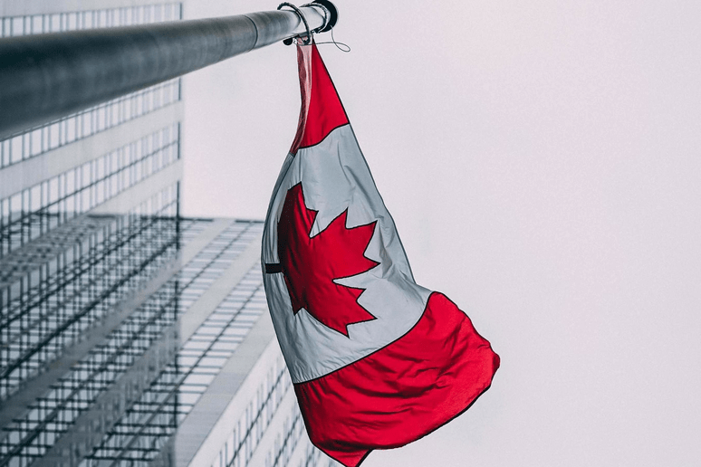 canadian flag with a city landscape in background