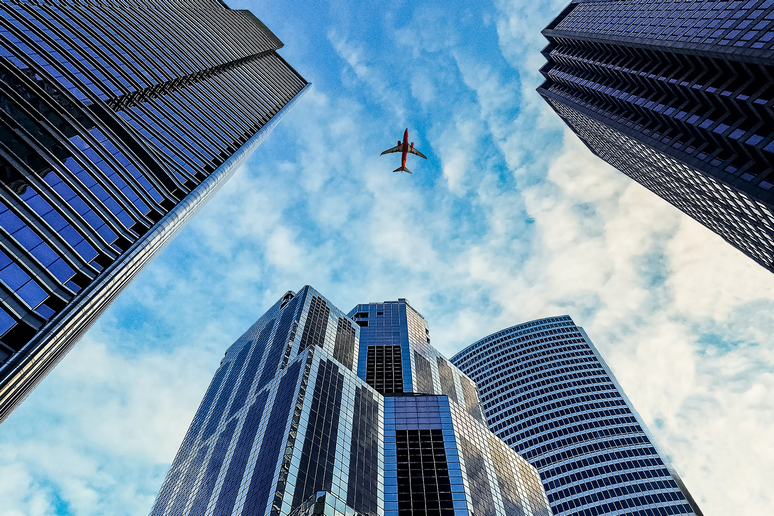 bottom-up view on skyscrapers with airplane